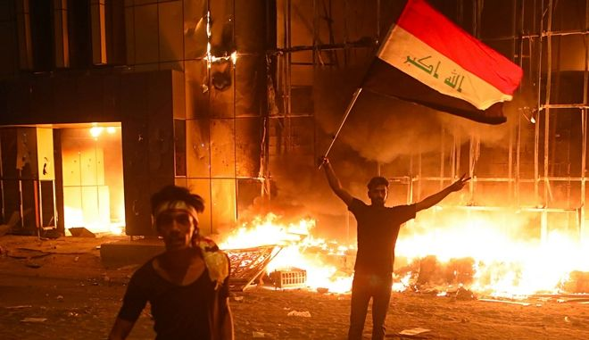 Διαδηλωτές στέκονται μπροστά από φλεγόμενο κτίριο στη Βασόρα