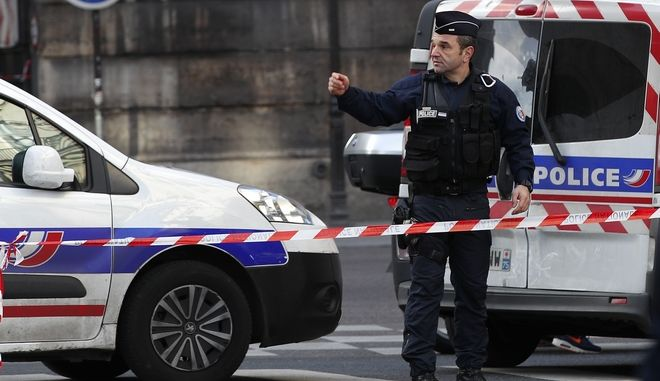 A police officer cordons off the area outside the Louvre museum near where a soldier opened fire after he was attacked in Paris, Friday, Feb. 3, 2017. Police say the soldier opened fire outside the Louvre Museum after he was attacked by someone, and the area is being evacuated. (AP Photo/Christophe Ena)