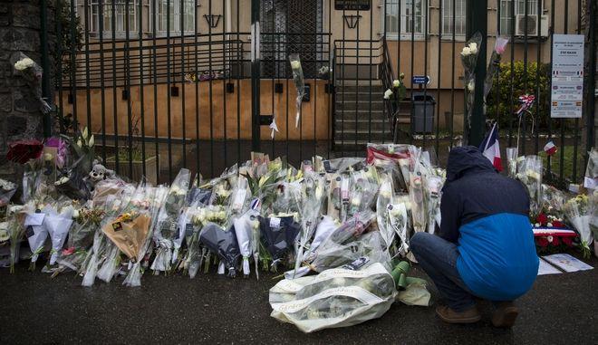 Ένας άνδρας αφήνει λουλούδια στην πύλη του αστυνομικού τμήματος της Καρκασόν στη μνήμη του ήρωα χωροφύλακα Αρνό Μπελτράμ