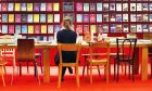 A woman sits at a table and reads at a stand at the Book Fair in Frankfurt, Germany, Wednesday, Oct. 19, 2016. The Frankfurt Book Fair lasts until Sunday, Oct.23. (AP Photo/Michael Probst)