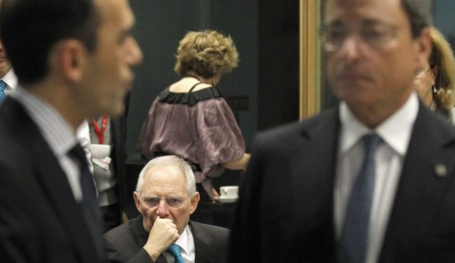 Germany's Finance Minister Wolfgang Schauble, centre, looks on as Cyprus Finance Minister Harris Georgiades, left, talks with European Central Bank President Mario Draghi, right, before the Informal meeting of ECOFIN Ministers in Dublin Castle, Ireland, Friday, April 12, 2013.  (AP Photo/Peter Morrison)