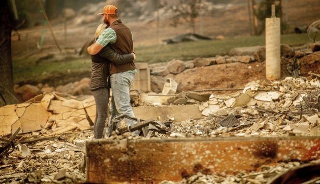 Ζευγάρι αγκαλιάζεται στα απομεινάρια του σπιτιού του, στο Πάραντάις της Καλιφόρνια