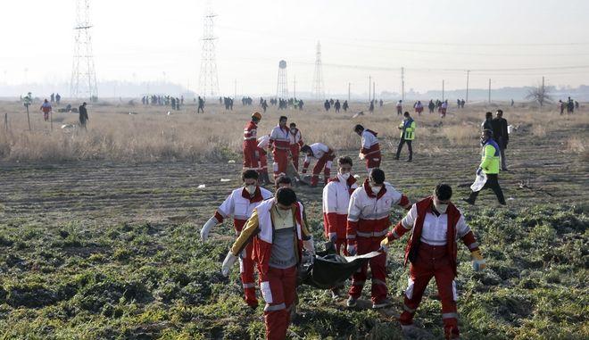 Διασώστες μεταφέρουν πτώματα από το μοιραίο αεροπλάνο.