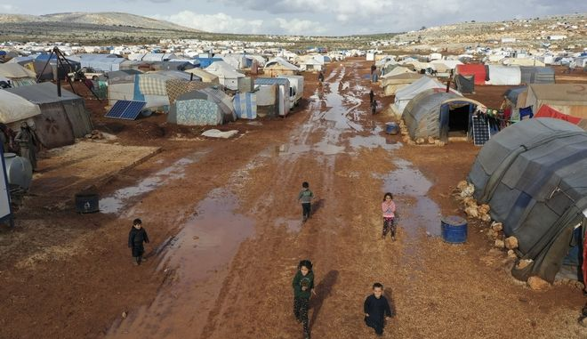 FILE - In this January 28, 2021 file photo, Syrian refugees walk through a camp for displaced muddied by recent rains near the village of Kafr Aruq, in Idlib province, Syria. Hundreds of thousands of Syrians face continued displacement each coming year if the conflict continues and economic conditions further deteriorate, the Norwegian Refugee Council, a prominent humanitarian organization said Monday, March 8, 2021. The Syrian conflict, which marks 10 years later this month, has resulted in the largest displacement crisis since World War II, the council said. (AP Photo/Ghaith Alsayed, File)