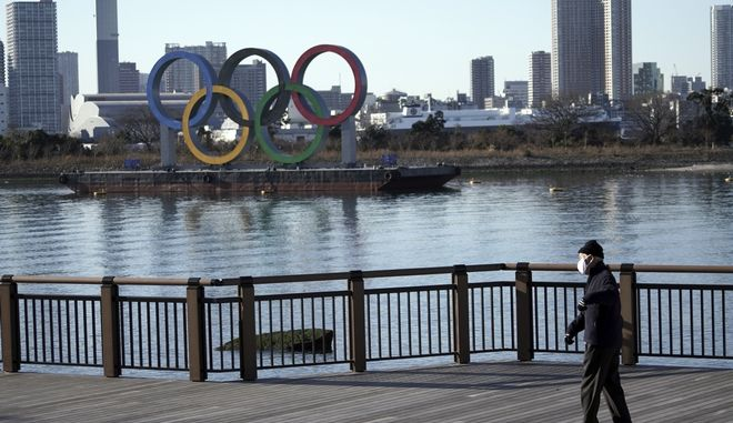 A man wearing a protective mask to help curb the spread of the coronavirus walks near the Olympic rings floating in the water in the Odaiba section in Tokyo Wednesday, Jan. 20, 2021. The Japanese capital confirmed more than 1,200 new coronavirus cases on Wednesday. (AP Photo/Eugene Hoshiko)