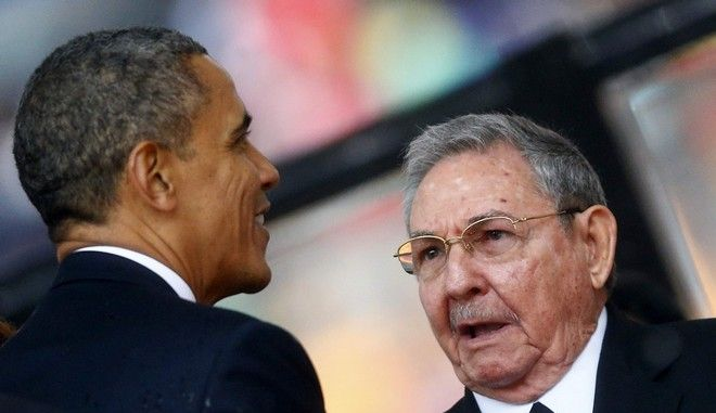 U.S. President Barack Obama (L) greets Cuban President Raul Castro before giving his speech at the memorial service for late South African President Nelson Mandela at the First National Bank soccer stadium, also known as Soccer City, in Johannesburg December 10, 2013. Obama shook the hand of Castro at a memorial for Nelson Mandela on Tuesday, a rare gesture between the leaders of two nations at loggerheads for more than half a century.  REUTERS/Kai Pfaffenbach (SOUTH AFRICA - Tags: POLITICS OBITUARY)