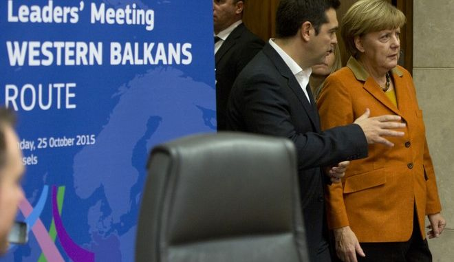 German Chancellor Angela Merkel, right, speaks with Greek Prime Minister Alexis Tsipras as they arrive for a round table meeting at an EU summit at EU headquarters in Brussels on Sunday, Oct. 25, 2015. EU leaders meet on Sunday to discuss refugee flows along the Western Balkans route. (AP Photo/Virginia Mayo)