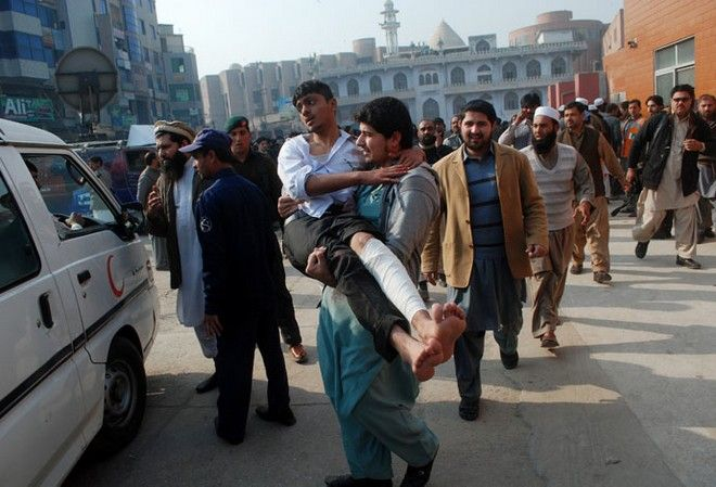 A man carries a student, who was injured during an attack by Taliban gunmen on the Army Public School, after he received treatment at a hospital in Peshawar, December 16, 2014. Taliban gunmen in Pakistan took hundreds of students and teachers hostage on Tuesday in a school in the northwestern city of Peshawar, military officials said.  REUTERS/Khuram Parvez (PAKISTAN - Tags: CRIME LAW CIVIL UNREST) - RTR4I6XT
