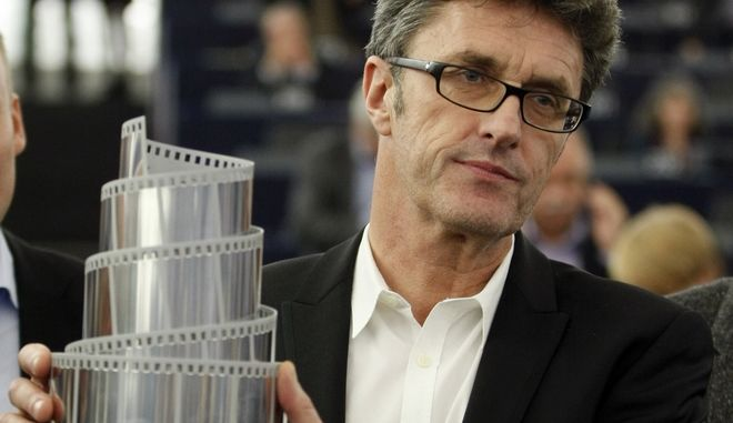 """FILE - In this Wednesday, Dec. 17, 2014 file photo, Polish director Pawel Pawlikowski holds the Lux Prize trophy awarded by the European Parliament for his film """"Ida"""" at the European parliament in Strasbourg, eastern France. A Polish movie vying for Golden Globe glory has raised hopes of a revival in the countrys grand cinematic traditions. Ida, a reflective movie about the legacy of the Holocaust in communist Poland, has unexpectedly been showered with international awards since its release in 2013 and is a nominee for best foreign language film in Sunday Jan. 11, 2015 Golden Globes and is widely expected to win a best foreign film nomination when Oscar candidates are announced next week. (AP Photo/Christian Lutz, File)"""