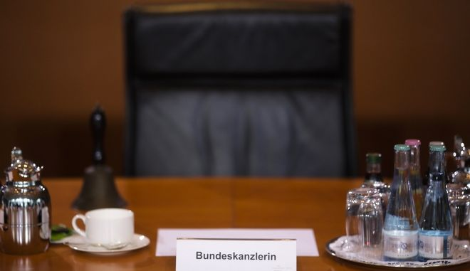 The empty seat of German Chancellor Angela Merkel is photographed prior to the first cabinet meeting of the German government after Sunday's general elections at the chancellery in Berlin, Wednesday, Sept. 27, 2017. (AP Photo/Markus Schreiber)