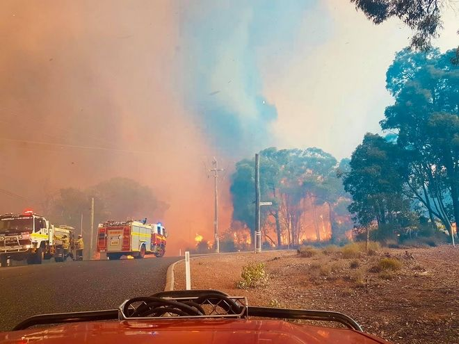 In this photo provided by Department of Fire and Emergency Services, firefighters attend a fire at Wooroloo, near Perth, Australia, Monday, Feb. 1, 2021. An out-of-control wildfire burning northeast of the Australian west coast city of Perth has destroyed an estimated 30 homes and was threatening more Tuesday, with many locals across the region told it is too late to leave. (Greg Bell/DFES via AP)