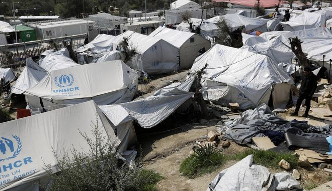 A migrant walks at the Moria refugee camp on the northeastern Greek island of Lesbos, Thursday, March 16, 2017. Over 62,000 refugees and migrants are stranded in Greece after a series of Balkan border closures and a European Union deal a year ago with Turkey to stop migrant flows. (AP Photo/Thanassis Stavrakis)