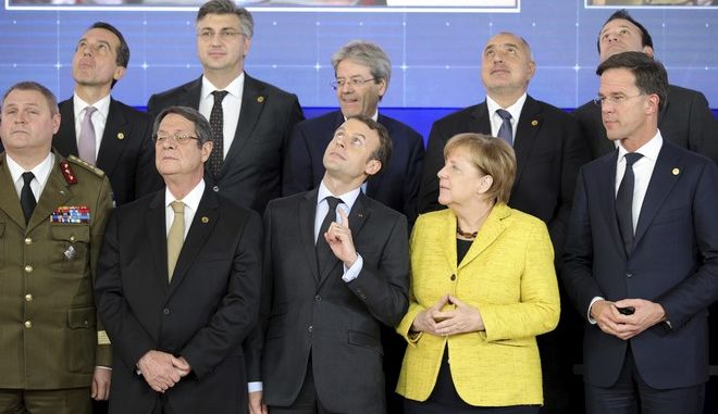 French President Emmanuel Macron, front center, and German Chancellor Angela Merkel, front second right, look up at a drone flying over their heads during a group photo at an EU summit at the Europa building in Brussels on Thursday, Dec. 14, 2017. European Union leaders are gathering in Brussels and are set to move Brexit talks into a new phase as pressure mounts on Prime Minister Theresa May over her plans to take Britain out of the 28-nation bloc. (AP Photo/Olivier Matthys)