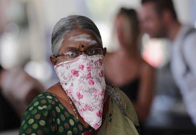 Ηλικιωμένη φοράει μάσκα για να προστατευτεί από τον νέο κοροναϊό