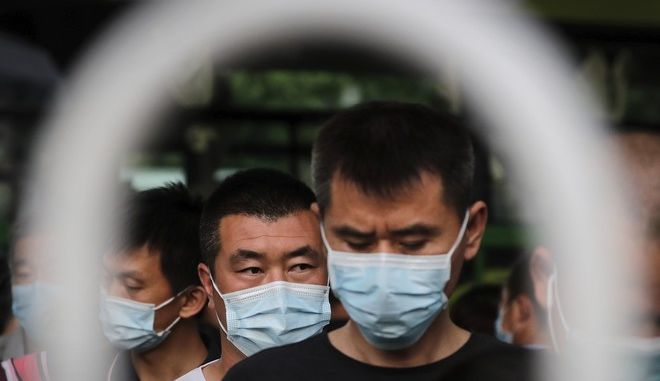 Επιβάτες σε στάση λεωφορείου στο Πεκίνο