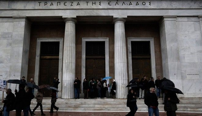 Protesters trying to protect themselves from the rain in the entrance of the Bank of Greece branch during demonstration against German Chancellor Angela Merkel's visit in Athens on Friday, April 11, 2014, as the German leader remains a contested figure in Greece because the chancellor is a vocal supporter of painful austerity policies inflicted on Greece.