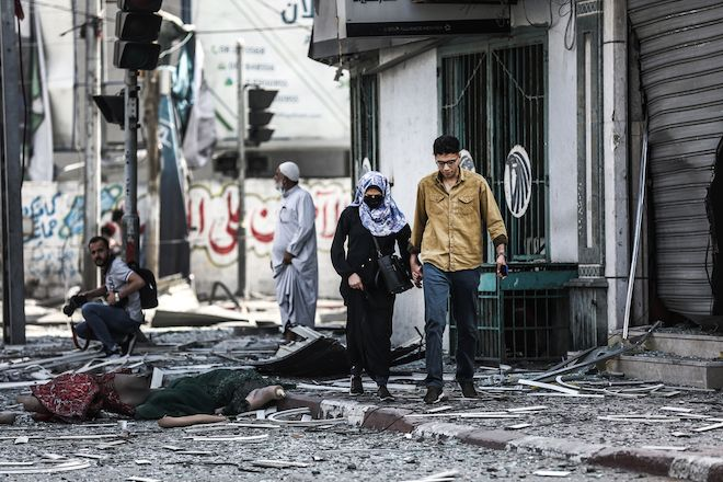 Palestinians walk amidst debris in Gaza city. 11 days of Israels intense aerial and ground bombardments has caused a huge impact on peoples lives in Gaza - people lost their family members, their homes and livelihoods and have suffered long-lasting physical and psychological injuries.