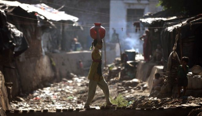 A young Indian girl walks back home carrying a canister of drinking water over her head filled from a public tap, in a shanty town on the outskirts of Jammu, India, Wednesday, June 4, 2014. There is no direct supply of potable water at homes in most of the poor neighborhoods in the country and people have to depend on regulated supply of water from public taps erected on roadsides, with a single tap catering to hundreds of households. (AP Photo/Channi Anand)