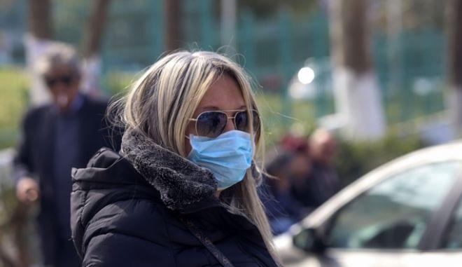 Γυναίκα με μάσκα έξω από νοσοκομείο (Φωτογραφία αρχείου)