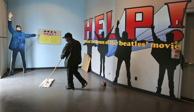 """A custodian cleans up at the entrance to an exhibit on the Beatles movie, """"Help"""" at the Rock and Roll Hall of Fame in Cleveland, Thursday, Nov. 15, 2007. The Rock and Roll Hall of Fame is paying tribute to the Fab Four's wacky film with an exhibit opening Saturday. (AP Photo/Mark Duncan)"""