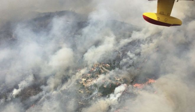 In this image made available by the Spanish Airforce on Sunday June 18, 2017, a Spanish firefighting plane flies over the fires in Pedrogao Grande, Portugal. More than 2,000 firefighters in Portugal battled Monday to contain major wildfires in the central region of the country, where one blaze killed 62 people, while authorities came under mounting criticism for not doing more to prevent the tragedy. (Spanish Airforce via AP)