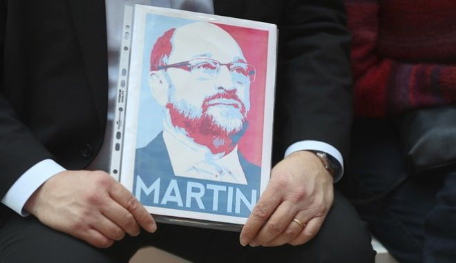 A supporter of the German Social Democratic Party, SPD, holds a picture of former President of the European Parliament Martin Schulz while waiting for a news conference at the party's headquarters in Berlin, Germany, Sunday, Jan. 29, 2017. Members of the SPD's national executive agreed Sunday to make Schulz their candidate for the chancellorship, a post that traditionally goes to the party which receives the greatest share of votes in a general election. (Kay Nietfeld/dpa via AP)