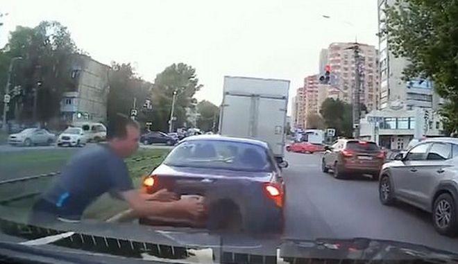 Η στιγμή που ο άνδρας πιάνει την ρόδα πριν αυτή καταλήξει στο αυτοκίνητό του