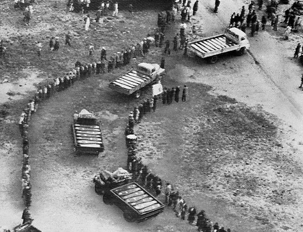 Trucks laden with coffins of black victims of South African shooting roll through lines of mourners during mass funeral ceremony at Sharpeville, south of Johannesburg, South Africa, March 21, 1960. No whites were permitted into the area during the funeral of 34 victims, who were killed by South African white police last week. (AP Photo)