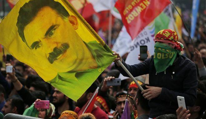 Εικόνα από συγκέντρωση Κούρδων στην Κωνσταντινούπολη τον Μάρτιο του 2018 με νεαρό να κρατάει σημαία με την εικόνα του Αμπντουλάχ Οτσαλάν