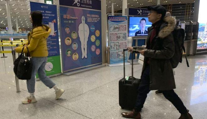 Ταξιδιώτες περνούν από σημείο ελέγχου στο αεροδρόμιο εξαιτίας της εξάπλωσης του νέου ιού.