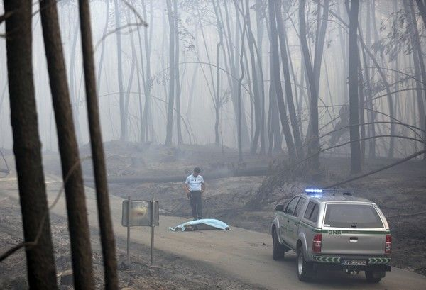 A policeman stands by a covered body on a dirt road outside Pedrogao Grande, central Portugal, Sunday, June 18 2017.  Raging forest fires in central Portugal killed more than 50 people, many of them trapped in their cars as flames swept over a road, in what the prime minister on Sunday called