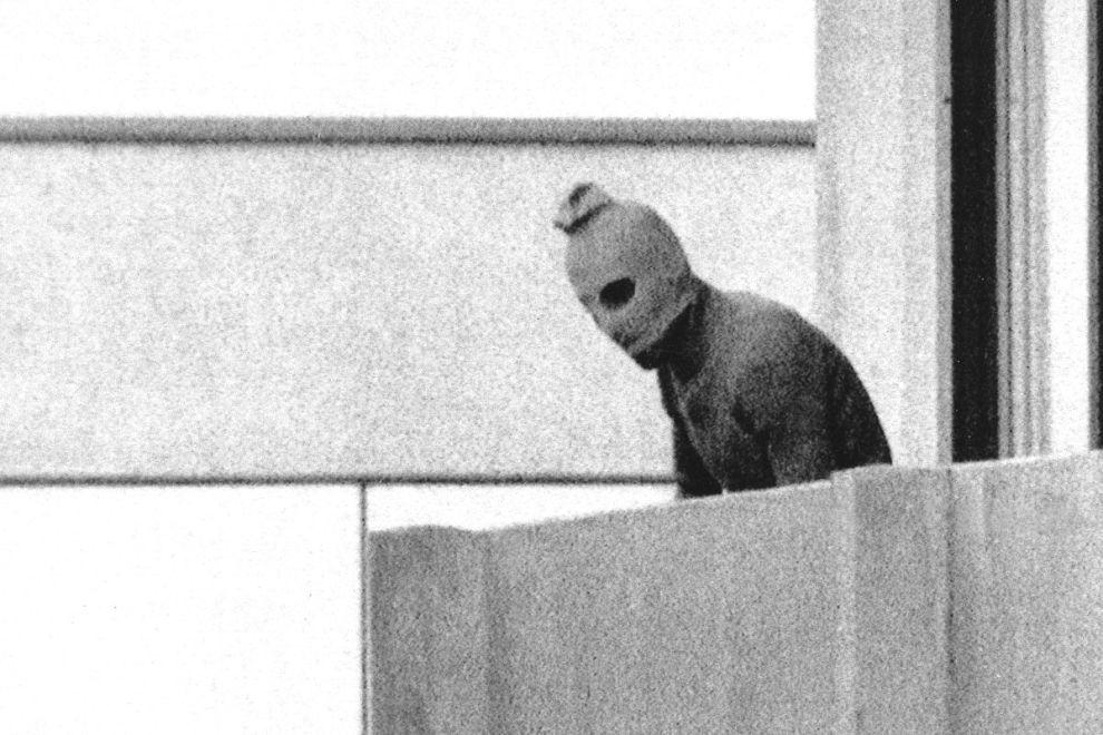 """Ένα από τα μέλη του """"Μαύρου Σεπτέμβρη"""" με κουκούλα, στο κτίριο όπου οι Παλαιστίνιοι τρομοκράτες κρατούσαν ομήρους τους Ισραηλινούς αθλητές (5/9/1972)."""