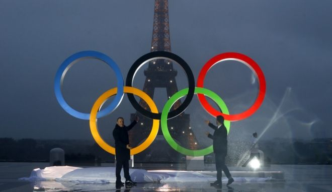Paris officials unveil a display of the Olympic rings on Trocadero plaza that overlooks the Eiffel Tower, after the vote in Lima, Peru, awarding the 2024 Games to the French capital, in Paris, France, Wednesday, Sept. 13, 2017. Paris will host the 2024 Summer Olympics and Los Angeles will stage the 2028 Games  a pre-determined conclusion that the International Olympic Committee has officially ratified in a history-making vote. (AP Photo/Francois Mori)