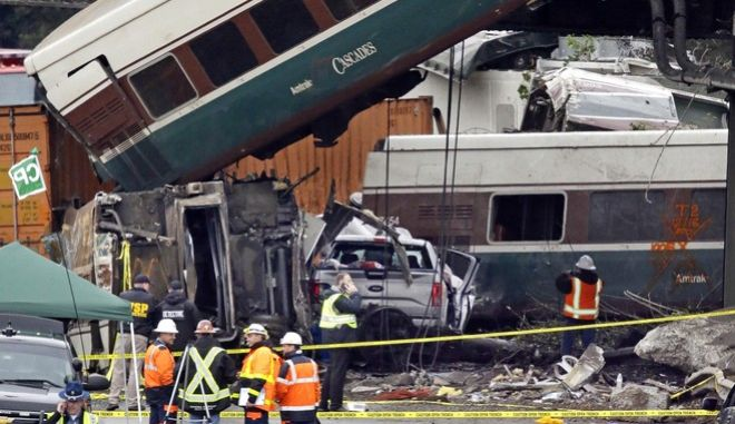 Cars from an Amtrak train that derailed above lay spilled onto Interstate 5 alongside smashed vehicles Monday, Dec. 18, 2017, in DuPont, Wash. The Amtrak train making the first-ever run along a faster new route hurtled off the overpass Monday near Tacoma and spilled some of its cars onto the highway below, killing some people, authorities said. (AP Photo/Elaine Thompson)