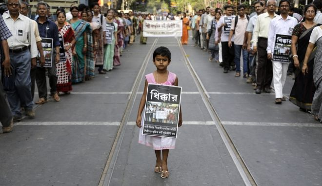 A girl walks with others in a silent procession protesting the gang rape of a nun at a convent at Ranaghat, in Kolkata, India, Saturday, March 21, 2015. A nun in her 70s was gang-raped by a group of bandits when she tried to prevent them from committing a robbery in the Convent of Jesus and Mary School in West Bengal state's Nadia district, according to police. Poster reads shame. (AP Photo/ Bikas Das)