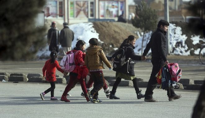 Afghan school children cross the road near to the site of a clash between gunmen and security forces in Kabul, Afghanistan, Monday, Dec. 18, 2017. Gunmen stormed a partially constructed building near an intelligence training center, triggering a gun-battle with security forces as detonations and shooting reverberated from the area. (AP Photo/Rahmat Gul)