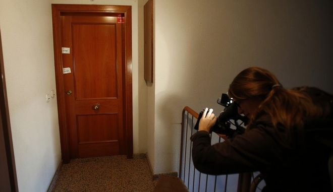 A journalist films a sealed door by the police where they found the badly decomposed body of a 7-year-old child in Girona, Spain, Friday, Jan. 8, 2016. American couple Bruce and Schrell Hopkins who were arrested after police found the badly body of their 7-year-old son at the family's apartment in northeastern Spain told a court Friday that the child suffered from asthma and did not wake up one morning but that the family didnt think he was dead. (AP Photo/Manu Fernandez)