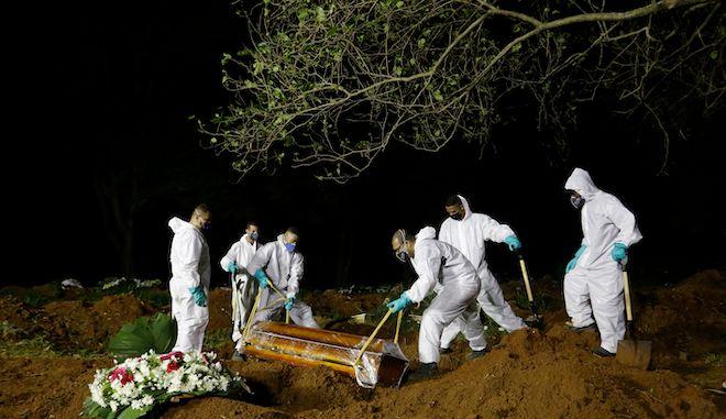 Ταφή ενός ατόμου που πέθανε από επιπλοκές της COVID-19, στο Σάο Πάολο της Βραζιλίας, 31 Μαρτίου 2021. Λόγω του αυξημένου αριθμού θανάτων, η ταφή έχει παραταθεί και για τη νύχτα