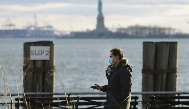 Άνθρωποι με μάσκα περπατούν στη Νέα Υόρκη