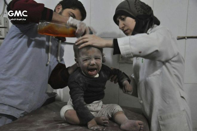 In this photo released on Wednesday Feb. 21, 2018, provided by the Syrian anti-government activist group Ghouta Media Center, which has been authenticated based on its contents and other AP reporting, shows Syrian paramedics treat a kids who was wounded during airstrikes and shelling by Syrian government forces, at a makeshift hospital, in Ghouta, suburb of Damascus, Syria. New airstrikes and shelling on the besieged, rebel-held suburbs of the Syrian capital killed at least 10 people on Wednesday, a rescue organization and a monitoring group said. (Ghouta Media Center via AP)