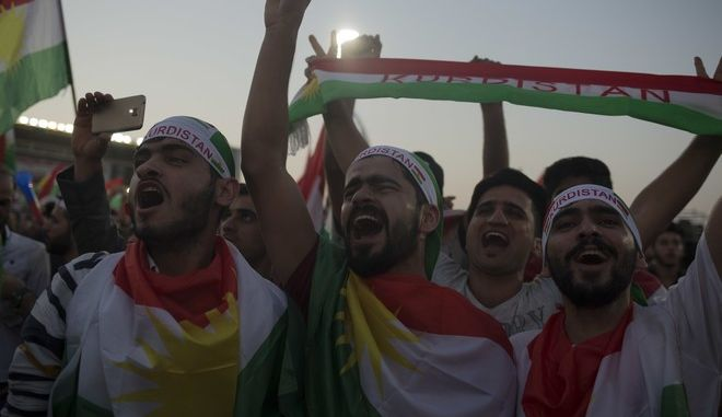 "Pro independence supporters wrapped in Kurdish flags chant at a referendum rally in Irbil, Friday, Sept. 22, 2017. Speaking to the crowd of thousands in the Irbil soccer stadium Kurdish president, Masoud Barzani said the fight against the Islamic State group in partnership with the Iraqi military will ""continue"" despite the vote. (AP Photo/Bram Janssen)"