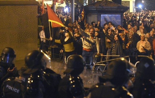 Police cordon blocks protestors to enter into the parliament building in Skopje, Macedonia, Thursday, April 27, 2017. Chaos swept into Macedonia's parliament Thursday as demonstrators stormed the building and attacked lawmakers to protest the election of a new speaker despite a months-old deadlock in efforts to form a new government. (AP Photo/Dragan Perkovski)