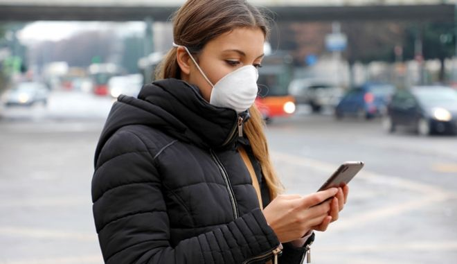 Κοπέλα με μάσκα για τον κορονοϊό κρατά το κινητό της τηλέφωνο