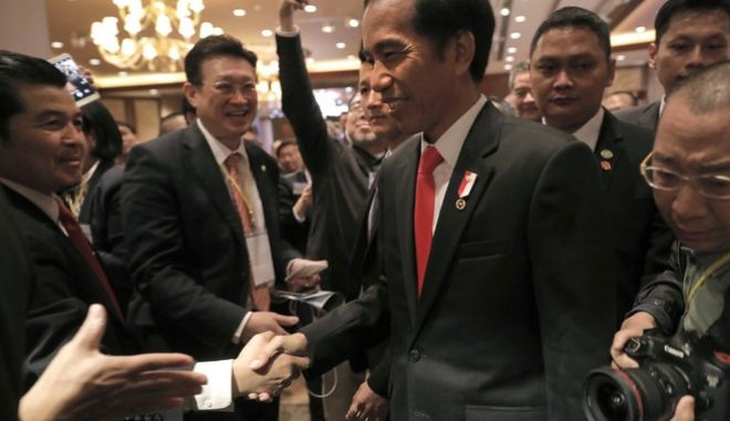 "Indonesian President Joko ""Jokowi"" Widodo, center, shakes hands with a businessman after a meeting at a hotel during his two-day visit in Hong Kong, Monday, May 1, 2017. (AP Photo/Vincent Yu)"
