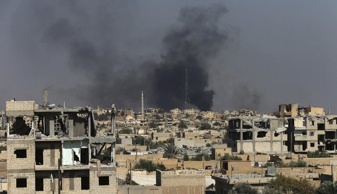 Black smoke rises from Raqqa city where U.S.-backed Syrian Democratic Forces fighters battle against Islamic State militants, in Raqqa, northeast Syria, Thursday, July 27, 2017. U.S.-backed Syrian fighters have captured almost half of the Islamic State group's de facto capital of Raqqa, but the push into the city in northern Syria has slowed due to stiff resistance and large amounts of explosives planted by the extremists, a spokeswoman for the fighters and monitors said Thursday. (AP Photo/Hussein Malla)