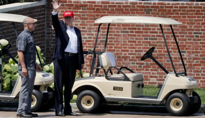 President Donald Trump waves to spectators as he walks out of his residence at the Trump National Golf Club during the third round of the U.S. Women's Open Golf tournament Saturday, July 15, 2017, in Bedminster, N.J. (AP Photo/Julie Jacobson)