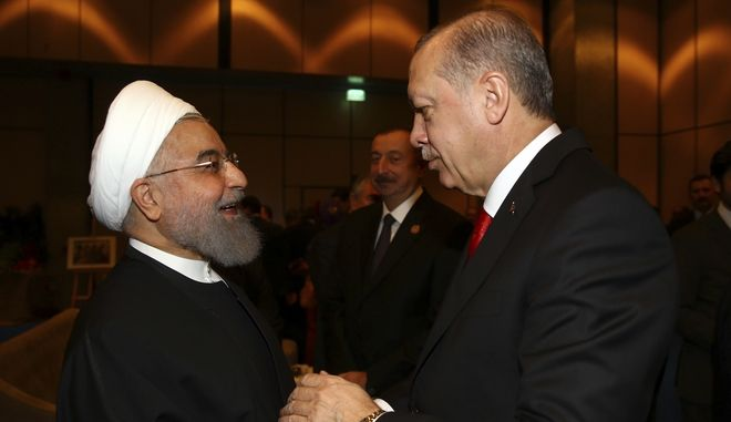 "Turkey's President Recep Tayyip Erdogan, right, welcomes Iran's President's Hassan Rouhani, left, prior to the opening session of the Organisation of Islamic Cooperation Extraordinary Summit in Istanbul, Wednesday, Dec. 13, 2017. Leaders and high-ranking officials of Muslim countries met in Istanbul to discuss the U.S. recognition of Jerusalem as Israel's capital. Erdogan_ term president of OIC, the umbrella organisation of 57-members, has been vehemently critical of the U.S. move and said the leaders would relay a ""strong message."" (Kayhan Ozer/Pool Photo via AP)"