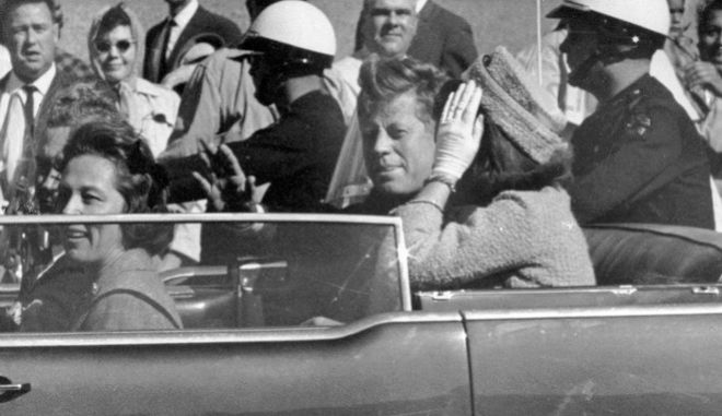 FILE - In this Nov. 22, 1963 file photo, President John F. Kennedy waves from his car in a motorcade approximately one minute before he was shot in Dallas. Riding with Kennedy are First Lady Jacqueline Kennedy, right, Nellie Connally, second from left, and her husband, Texas Gov. John Connally, far left. The National Archives has until Oct. 26, 2017, to disclose the remaining files related to Kennedy's assassination, unless President Donald Trump intervenes. (AP Photo/Jim Altgens, File)