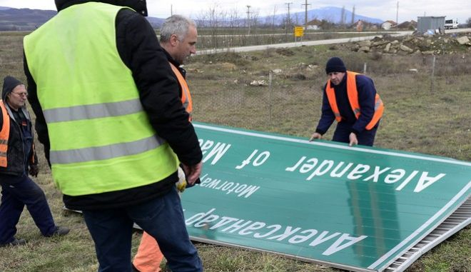 Workers remove a road sign that reads ''Alexander of Macedonia'' on the highway linking the capital Skopje with northern Greece, on Wednesday, Feb. 21, 2018. Macedonian authorities have begun replacing road signs on the country's main highway named by the previous government after the ancient warrior king Alexander the Great, in a goodwill gesture toward neighboring Greece. (AP Photo)