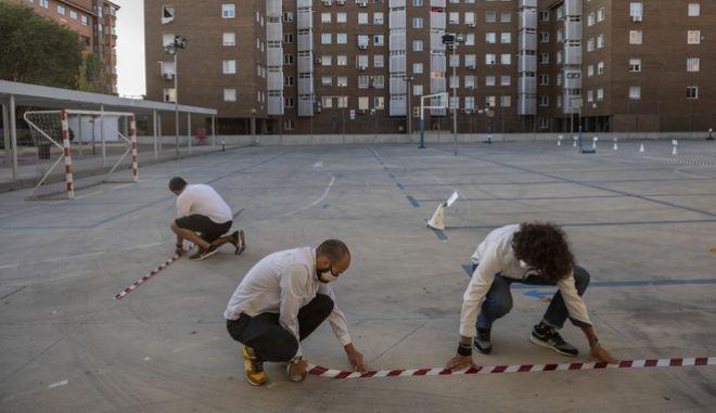Καθηγητές στη Μαδρίτη κολούν στο προαύλιο σχολείου κορδέλες σήμανσης για τη διατήρηση αποστάσεων